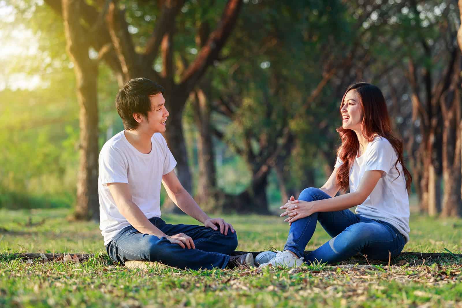 Ein Mann und eine Frau sitzen im Gras und reden