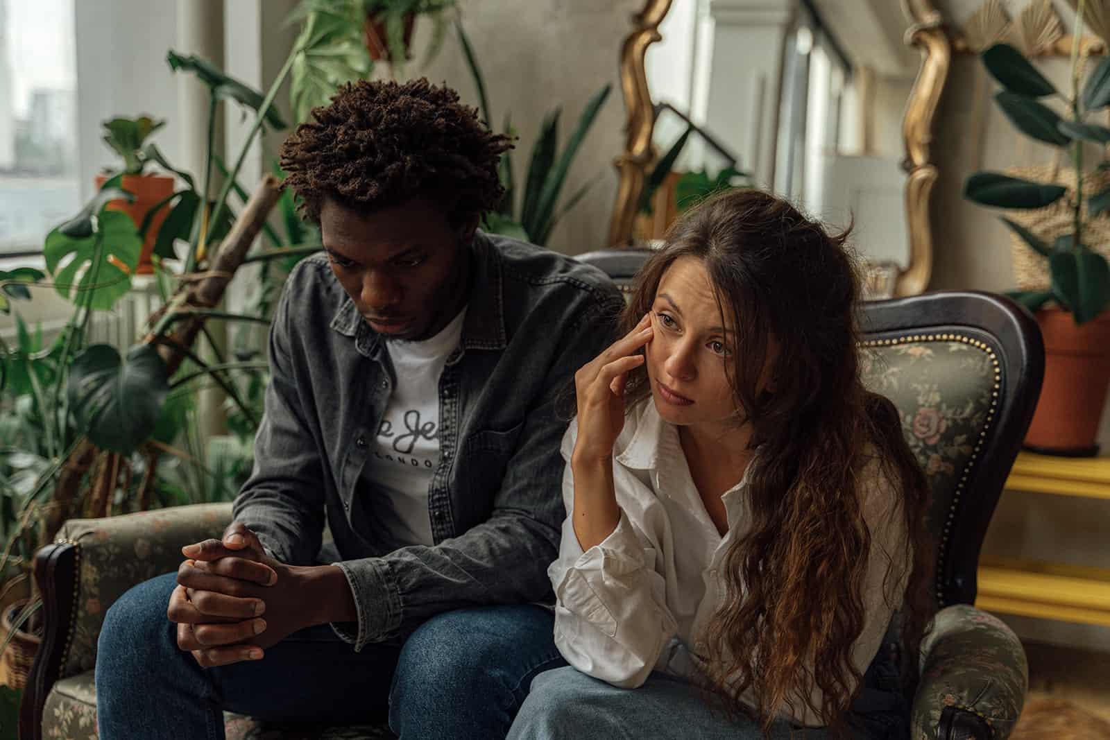Ein Mann und eine Frau sitzen zusammen auf dem Sessel und sehen beide gelangweilt aus