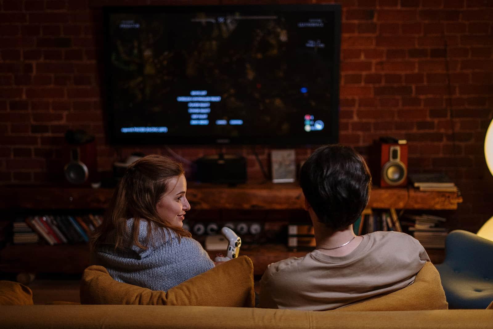 Ein Mann und eine Frau spielen das Spiel auf der PlayStation und sitzen auf der Couch