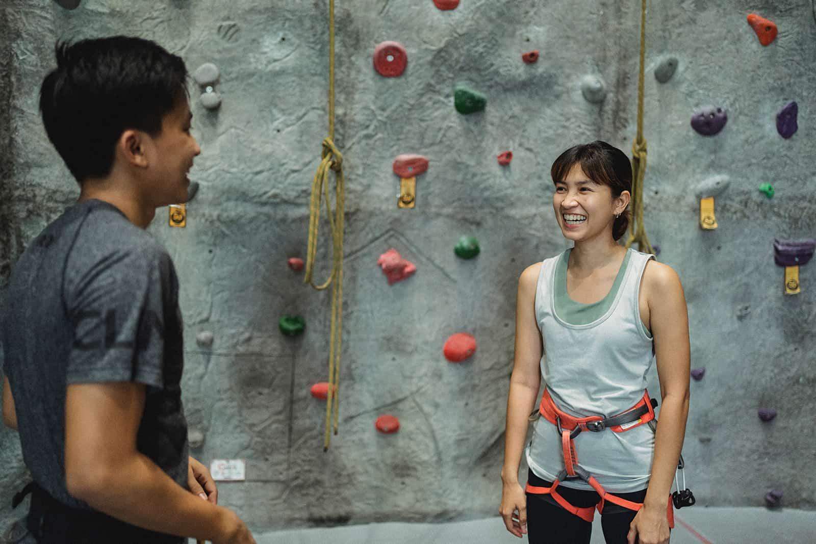 Ein Mann und eine Frau stehen vor einer Kletterwand und reden