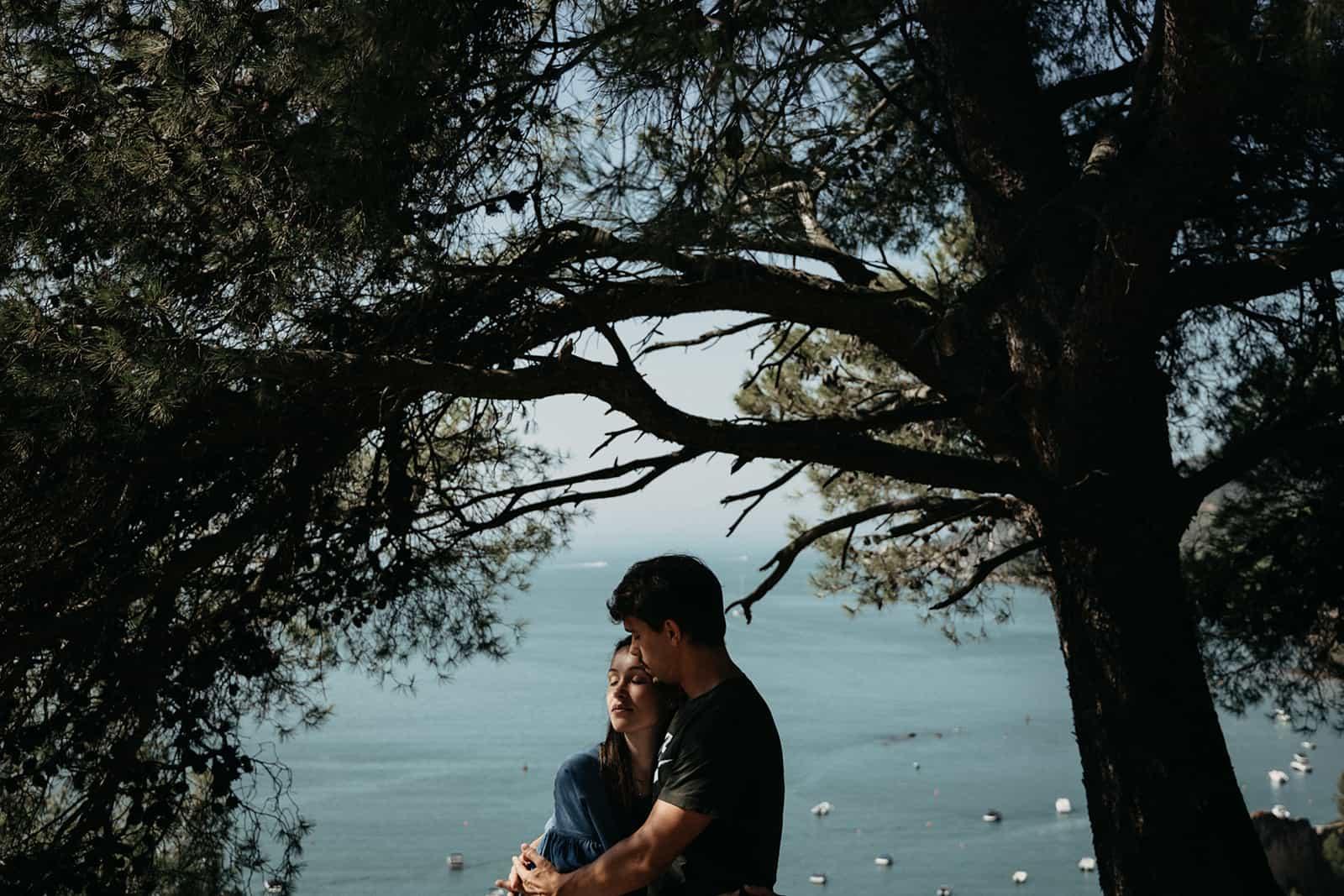 Ein Mann und eine Frau umarmen sich in der Nähe des Baumes mit Blick auf das Meer