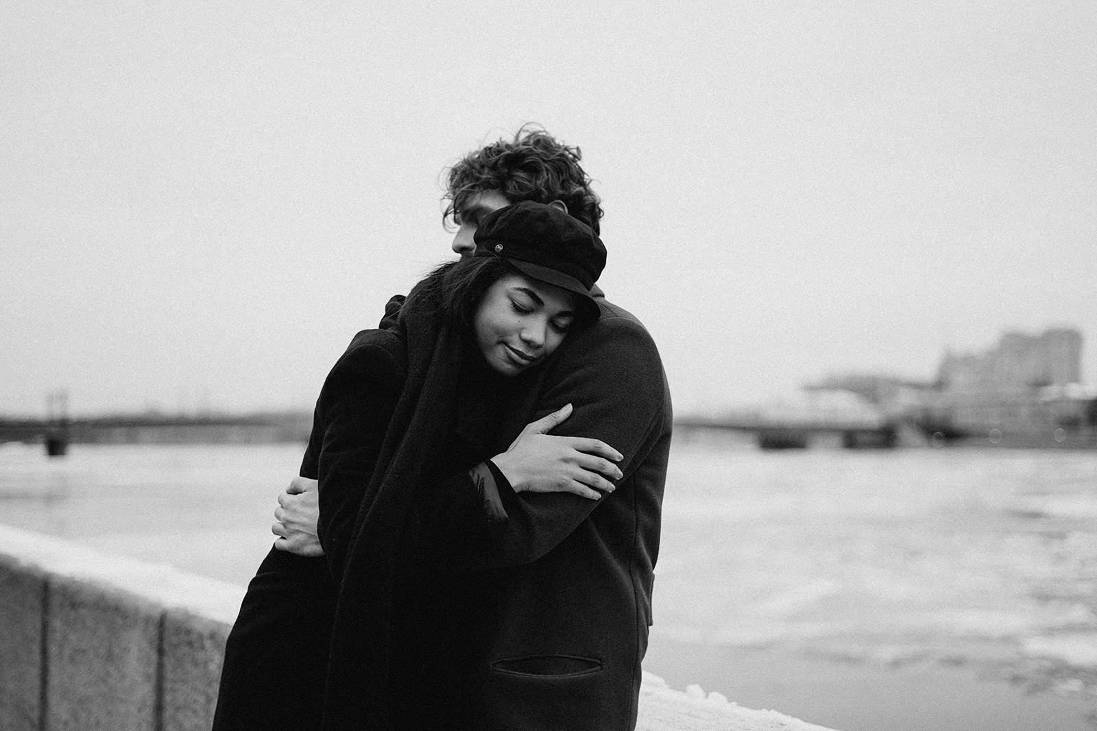 Ein Mann und eine Frau umarmen sich, während sie in der Nähe des Flusses stehen