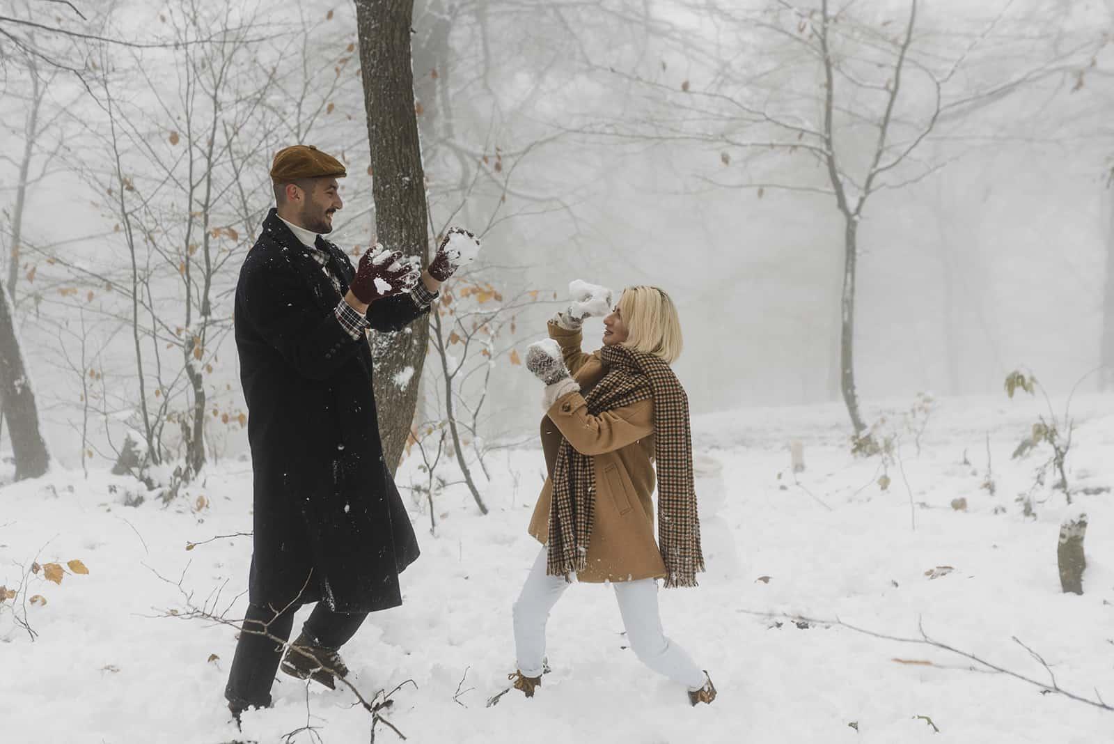 Ein Mann und eine Frau werfen sich im Park Schneebälle zu