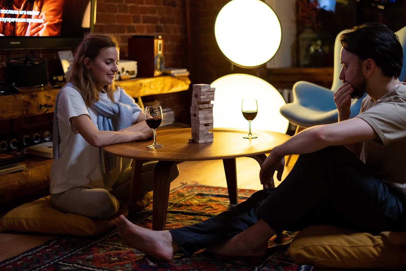 Ein Paar spielt zu Hause Jenga und trinkt abends Wein