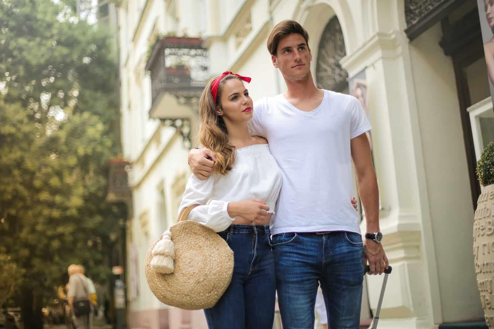 Ein Paar umarmt sich und geht mit einem Gepäck durch die Stadt