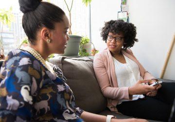 zwei Kolleginnen unterhalten sich auf der Couch