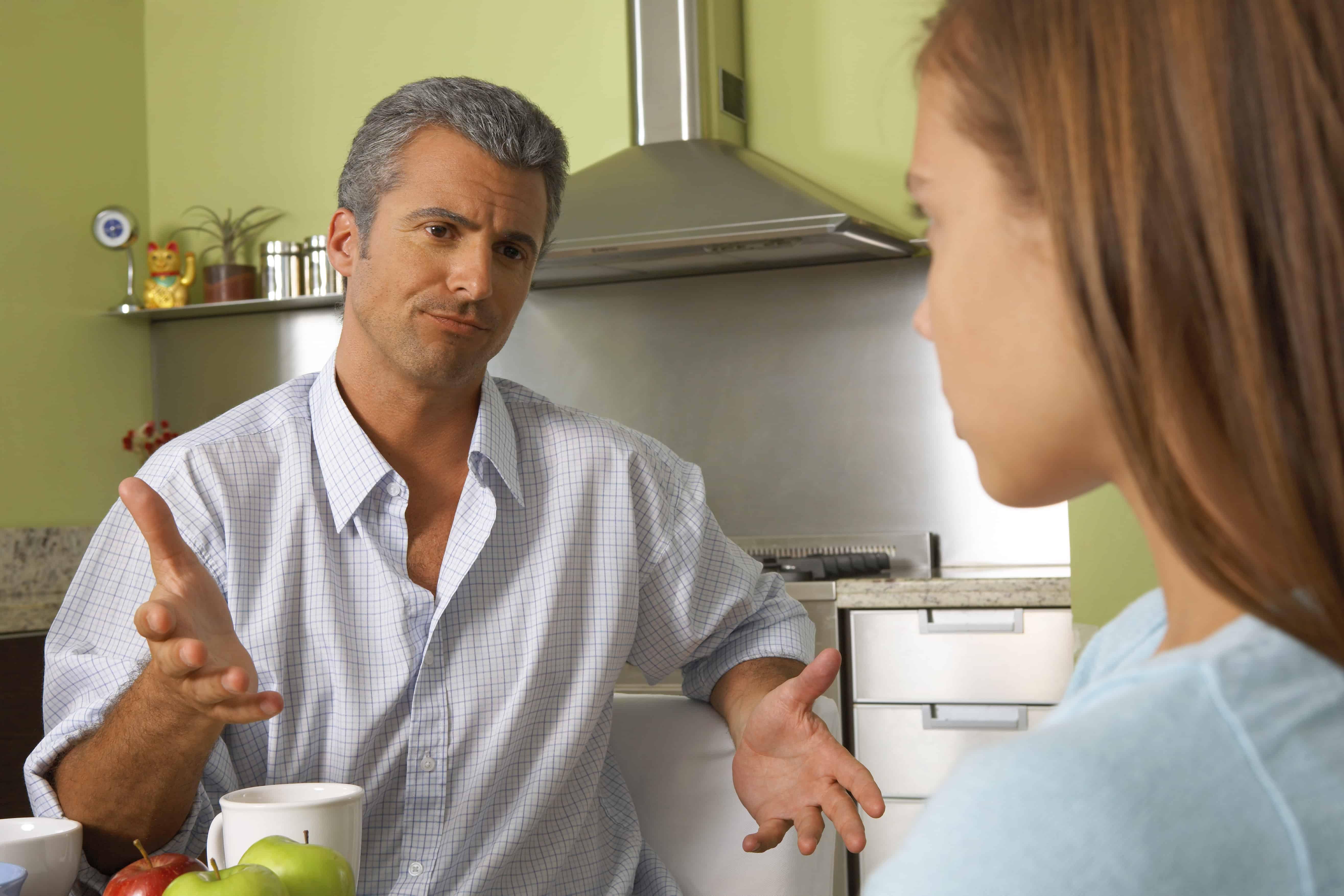Ein Vater unterhält sich mit seiner Tochter am Tisch in der Küche