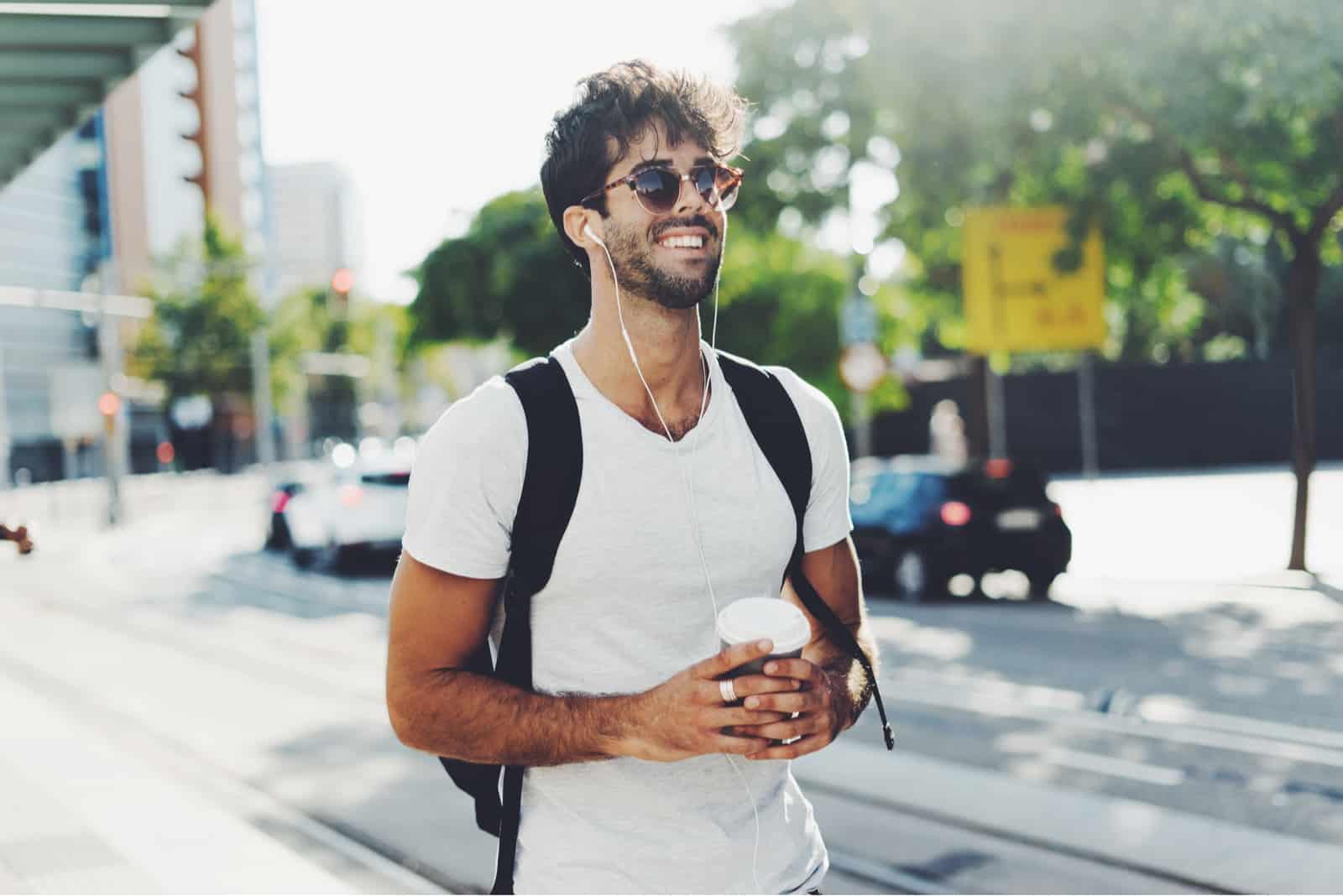 Ein attraktiver Mann geht die Straße entlang und hört Musik über Kopfhörer