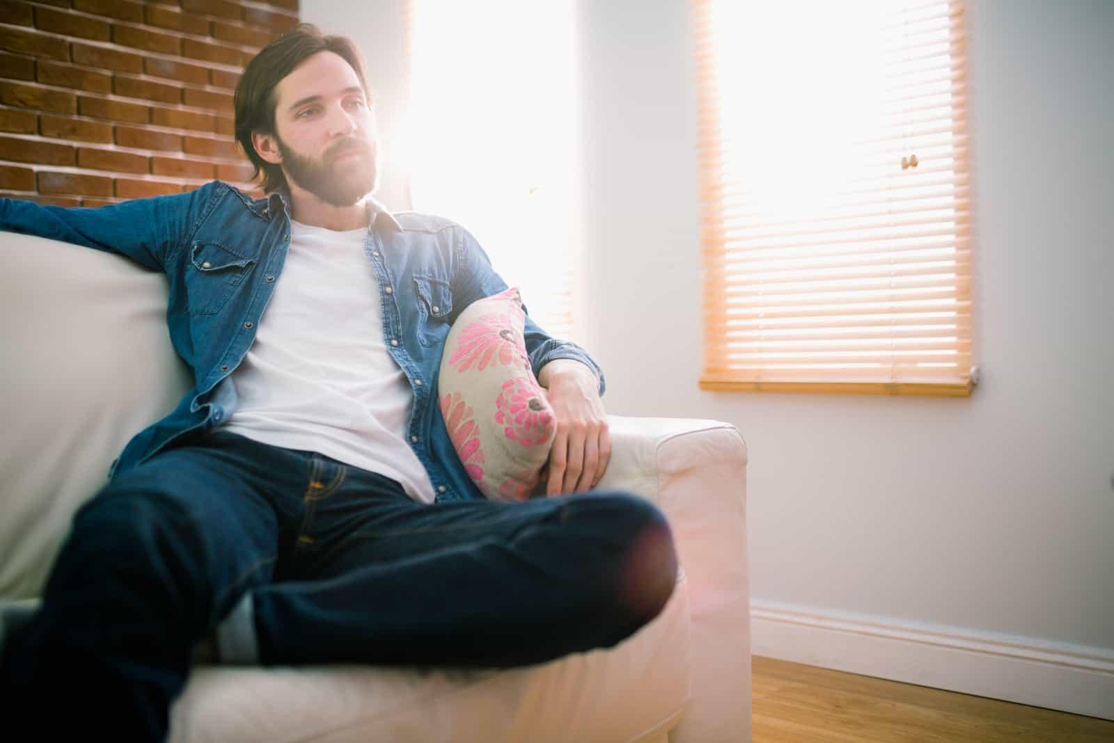 Ein bärtiger Mann sitzt auf der Couch und denkt nach