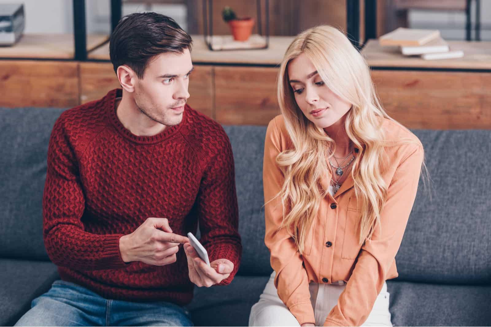 Ein eifersüchtiger Mann zeigt einer Frau auf einem Smartphone etwas