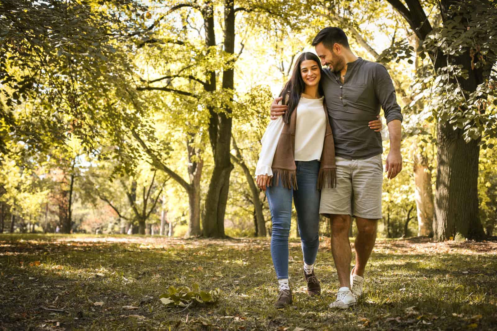 Ein glückliches Liebespaar geht durch den Park und umarmt sich