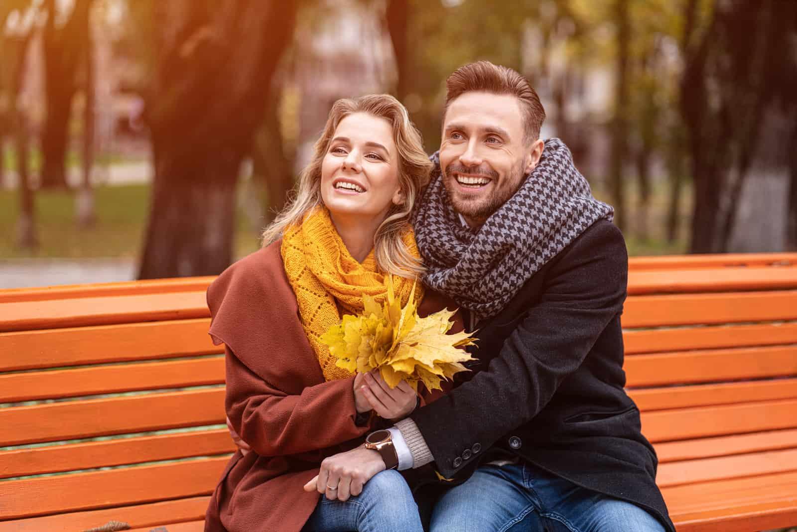 Ein glückliches Liebespaar sitzt auf einer Parkbank