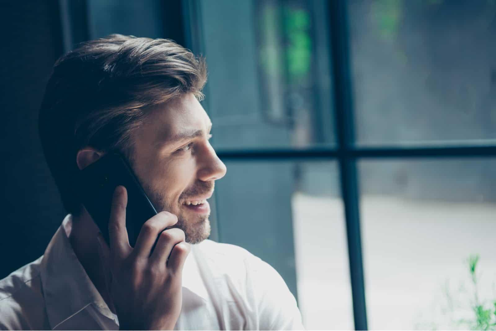 Ein lächelnder Mann am Fenster spricht auf einem Handy