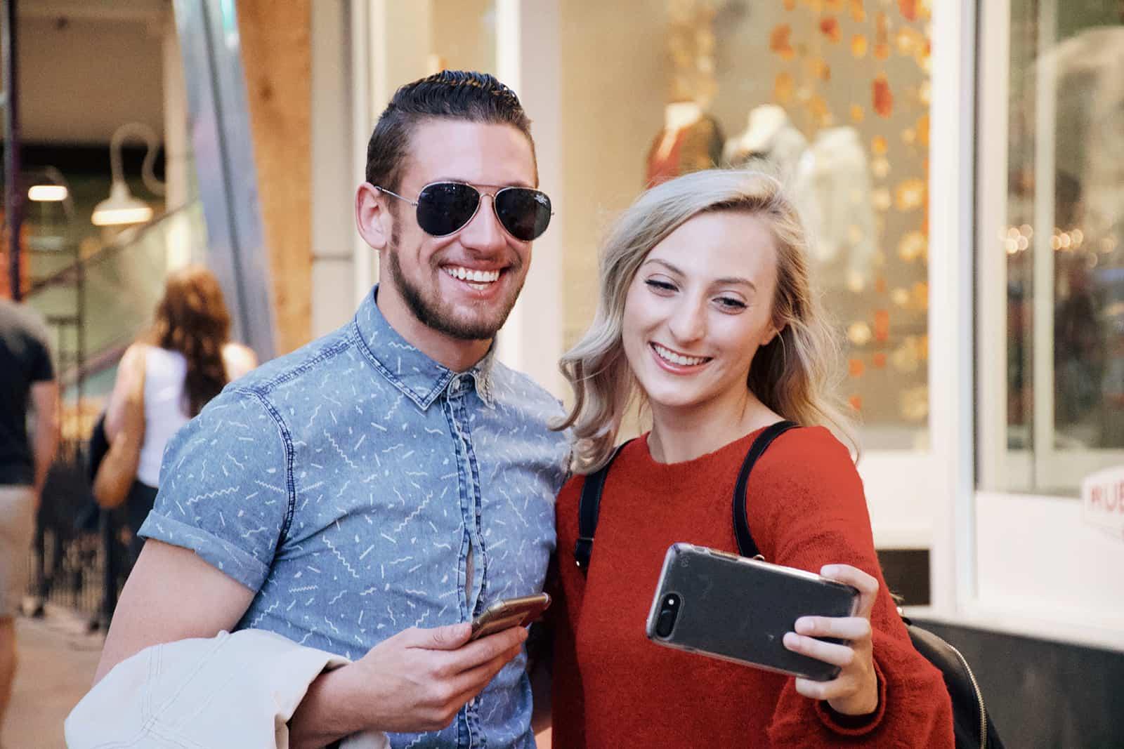 Ein lächelnder Mann und eine Frau machen ein Selfie, während sie im Einkaufszentrum stehen
