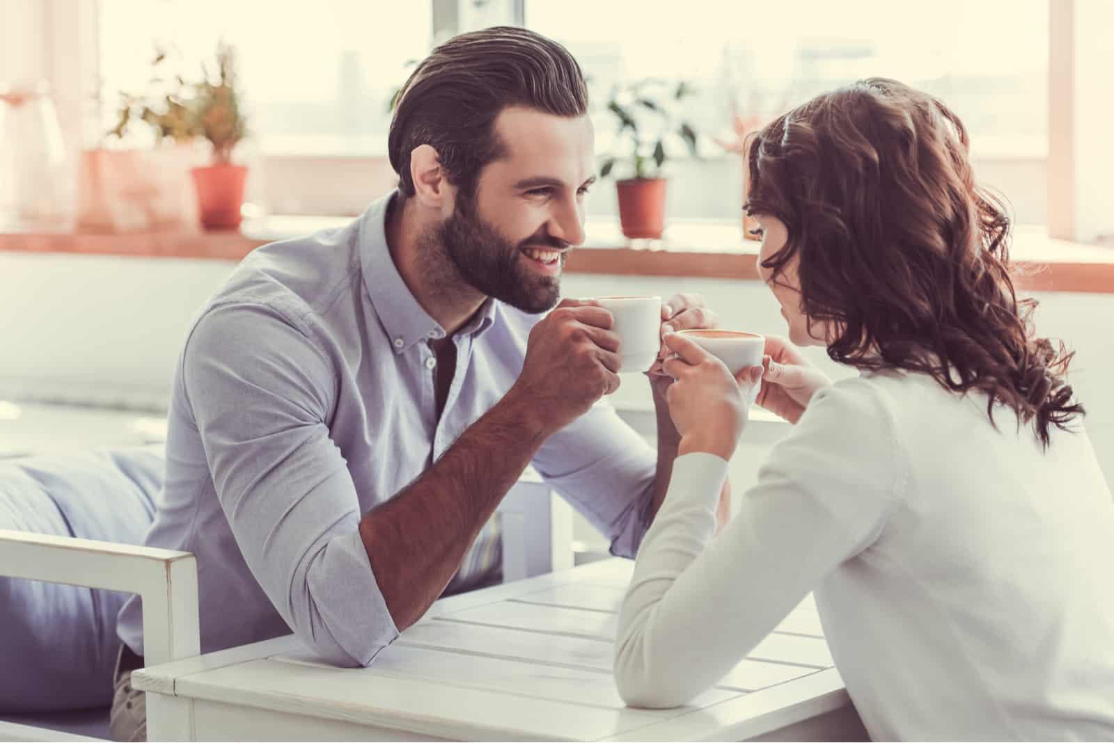 Ein lächelndes Paar flirtet bei einem Treffen in einem Café