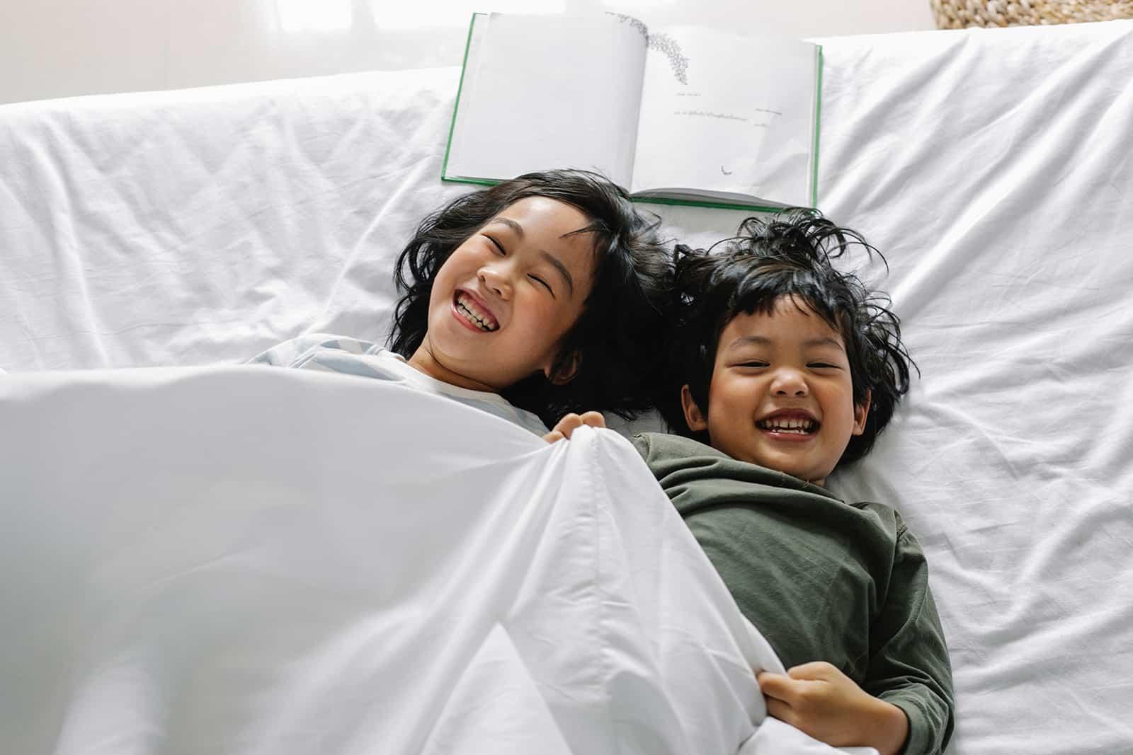 Ein lachender Bruder und eine lachende Schwester liegen im Bett neben dem Buch