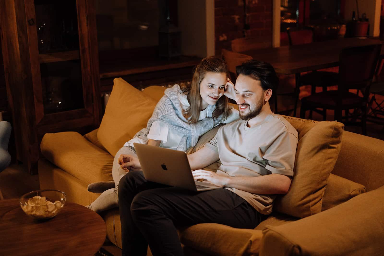 Ein liebevolles Paar wählt einen Film aus, den es auf dem Laptop auf der Couch sehen kann