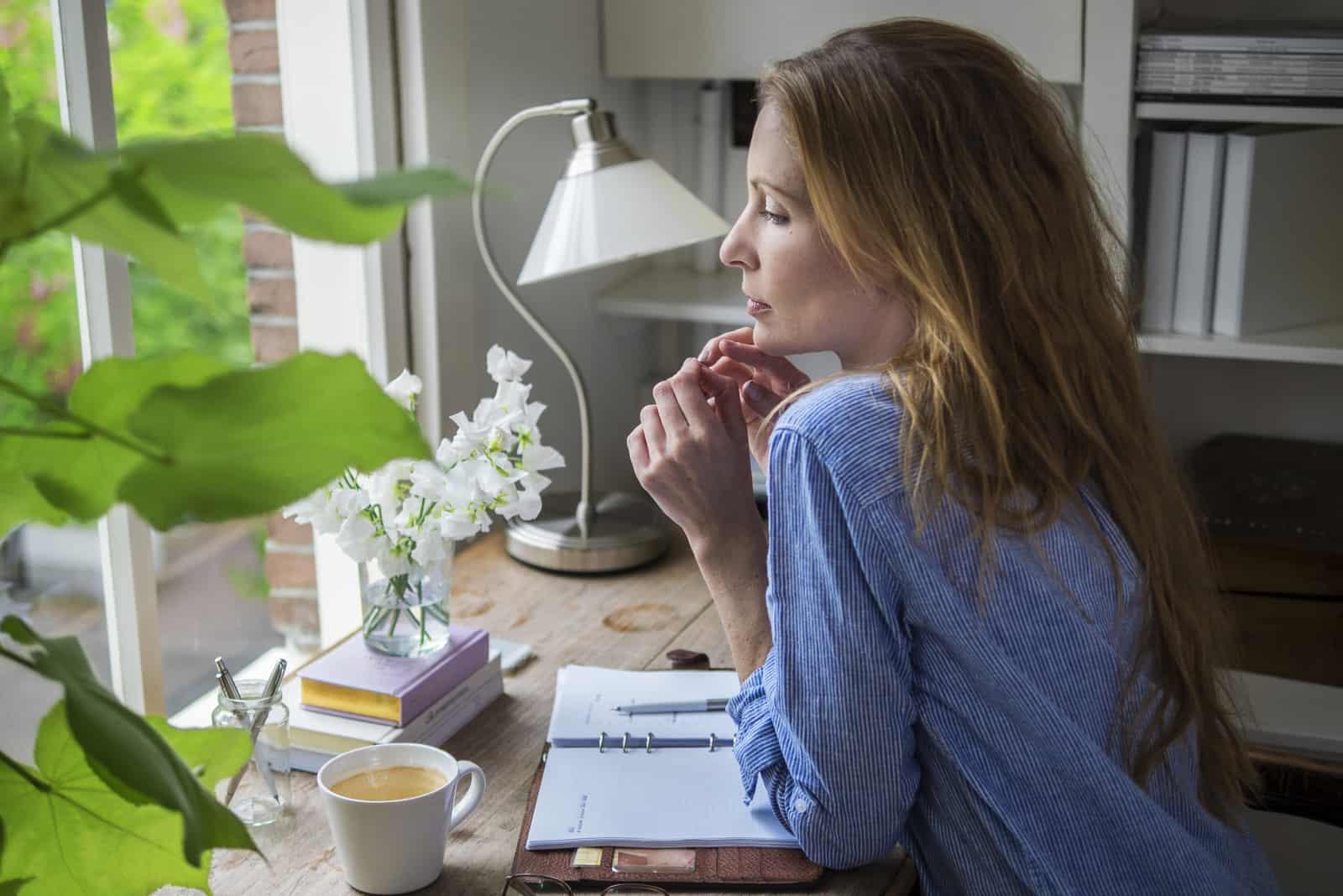 Eine Frau in einem Jeanshemd sitzt an ihrem Schreibtisch, trinkt Kaffee und denkt nach