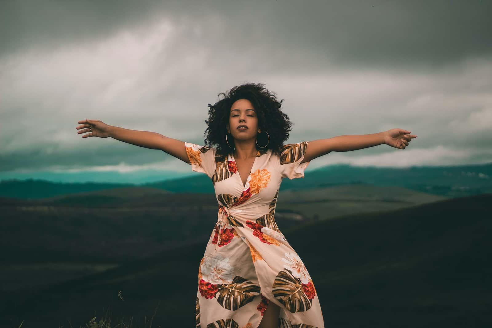 Eine Frau mit geschlossenen Augen stand im Wind auf dem Feld