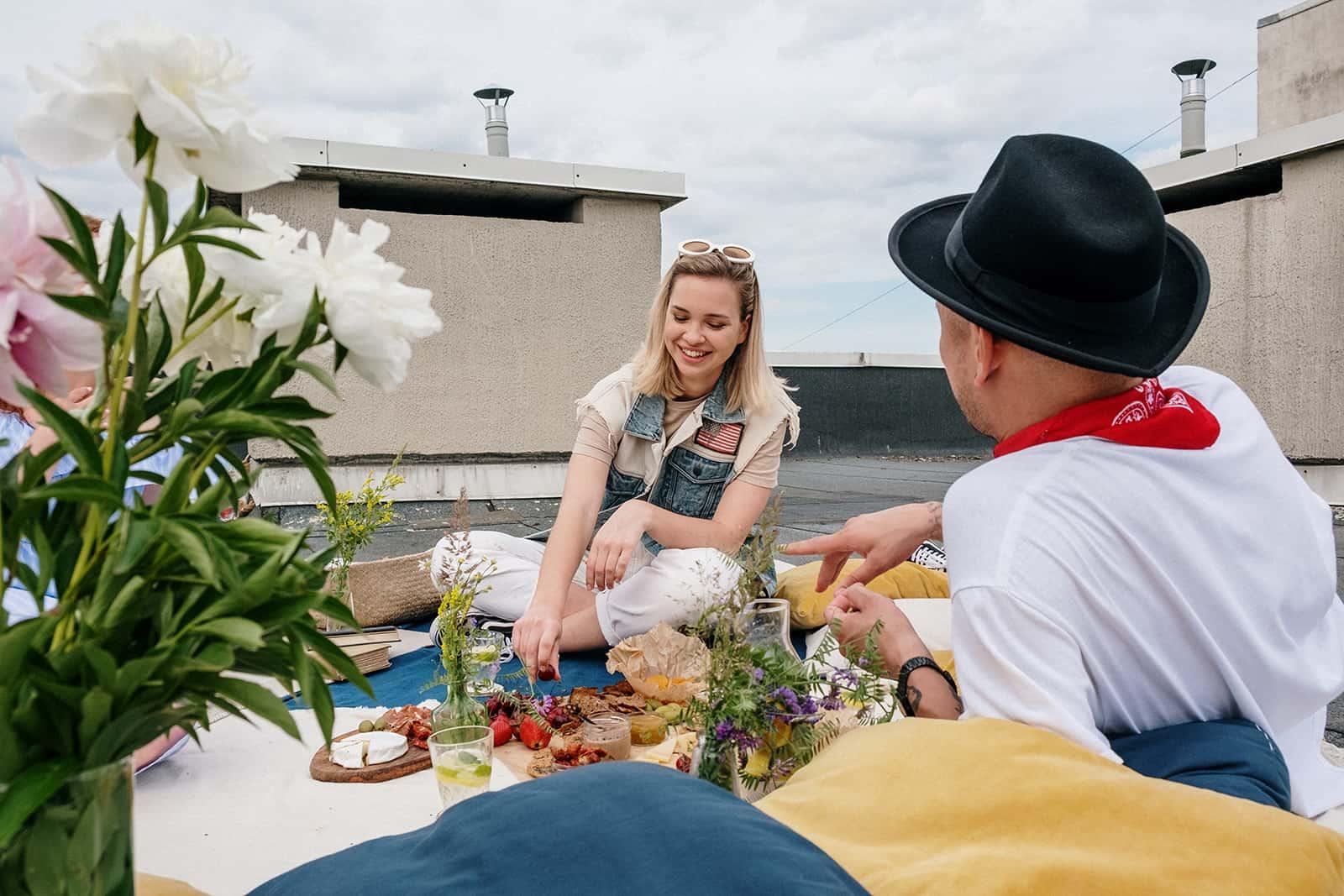 Eine Frau und ein Mann unterhalten sich über ein Date, das auf der Decke auf dem Dach sitzt