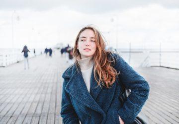 Porträt einer Blondine in einem blauen Mantel