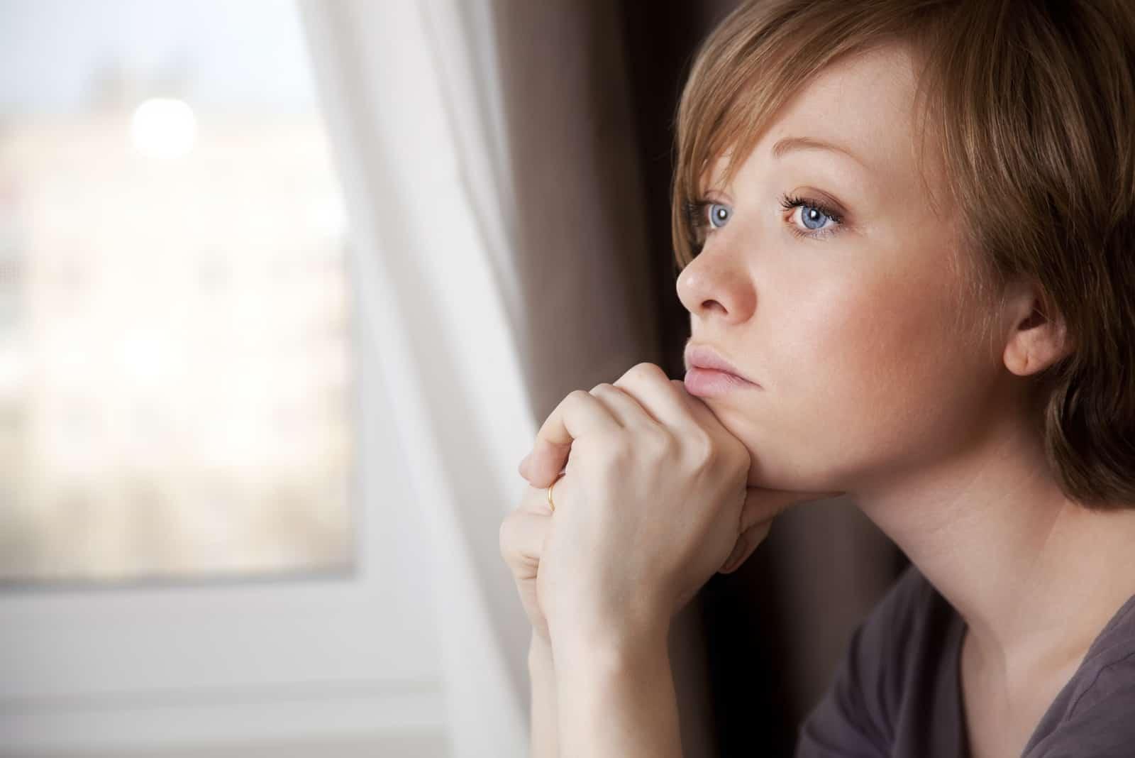 Eine kurzhaarige Frau sitzt am Fenster und denkt nach