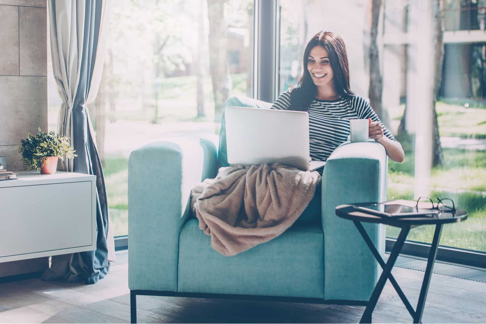 Eine lächelnde Frau in einem Sessel trinkt Kaffee und benutzt einen Laptop