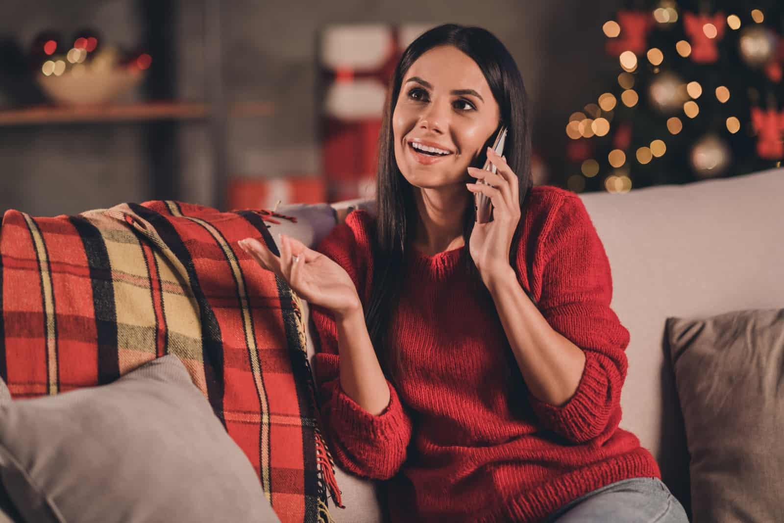 Eine lächelnde Frau sitzt auf der Couch und spricht auf ihrem Smartphone
