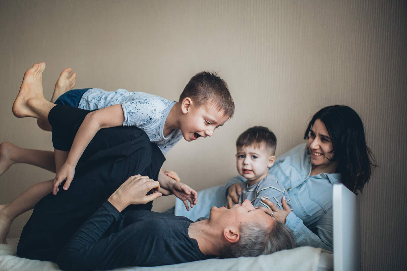 Eltern spielen mit ihren Söhnen auf dem Bett