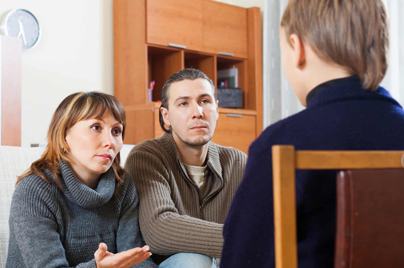 Eltern sprechen mit ihrem Kind, das auf dem Stuhl vor ihnen sitzt
