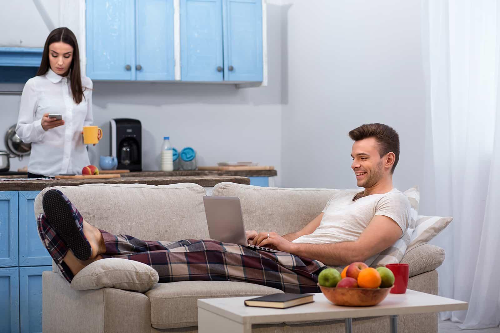 Fauler Ehemann mit einem Laptop auf der Couch, während seine Frau in der Küche steht und sich auf die Arbeit vorbereitet