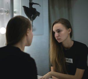 eine ernste Frau, die sich in den Spiegel schaut