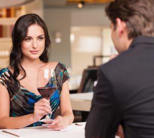 eine verführerische Frau, die ein Glas Wein hält und mit einem Mann sitzt