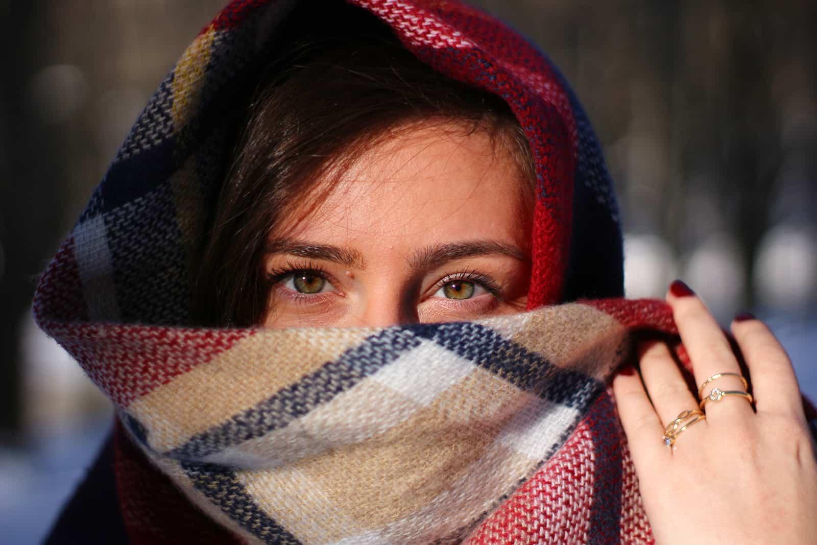 Frau bedeckt ihr Gesicht mit dem Kopftuch und hält es mit der Hand