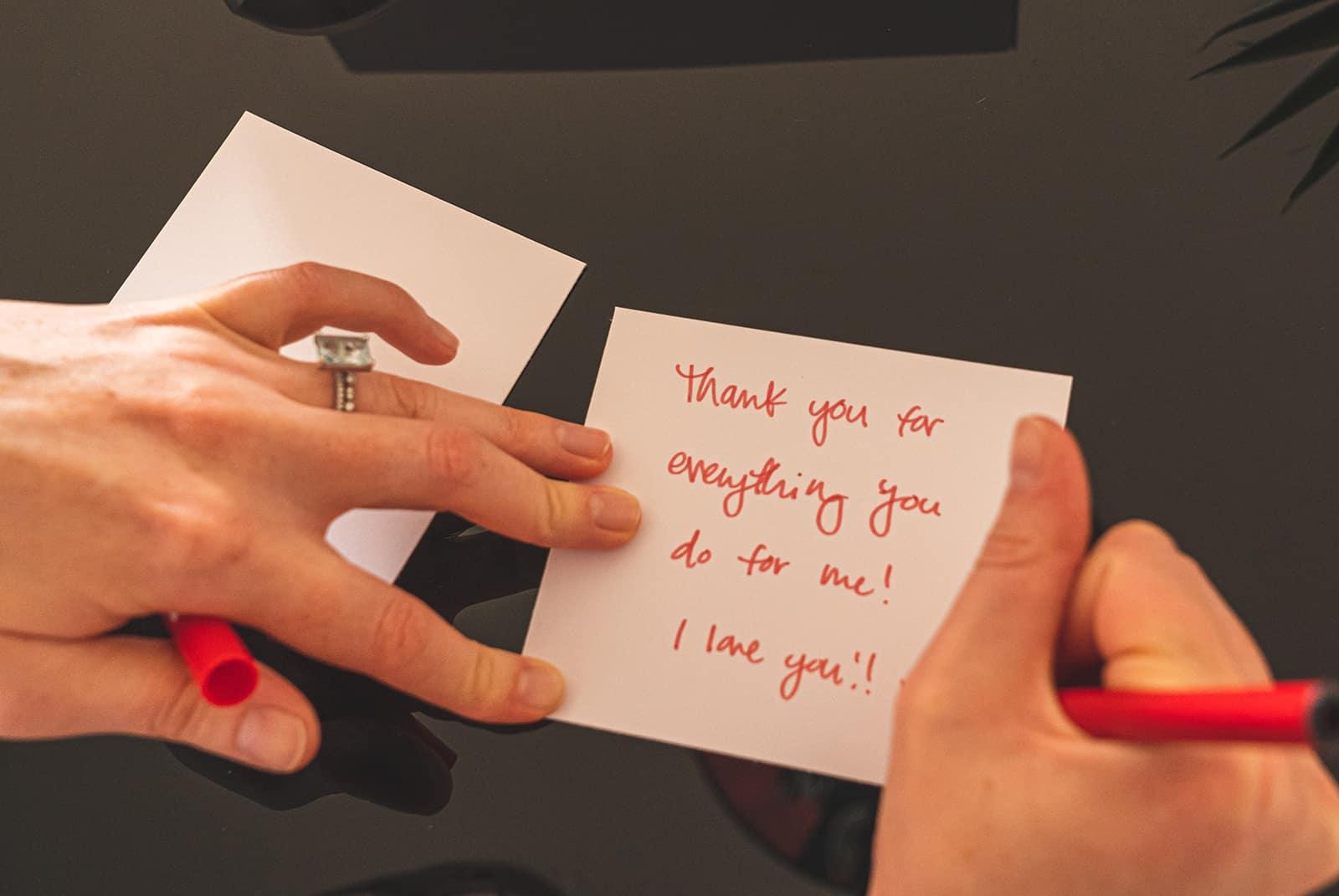 Frau, die eine Nachricht auf eine Notiz mit einem roten Stift schreibt