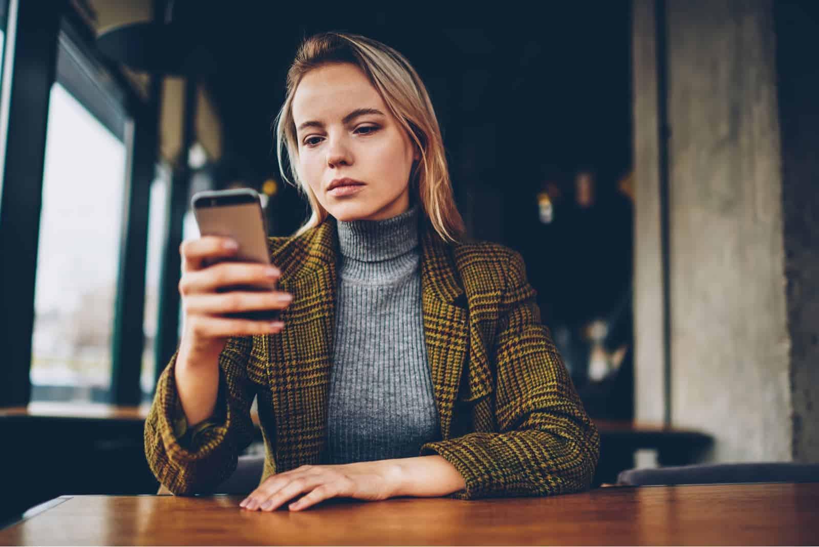 Frau sitzt am Tisch und hält ihr Handy