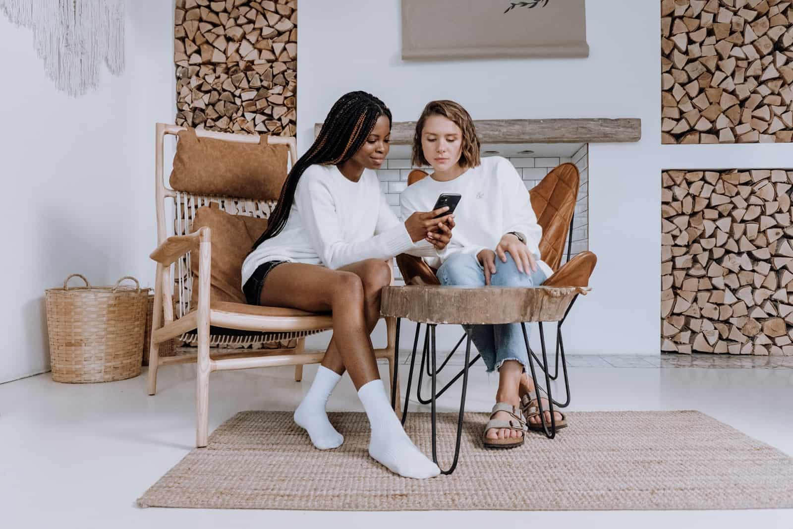Frau zeigt etwas auf einem Smartphone zu ihrer Freundin, die neben ihr sitzt
