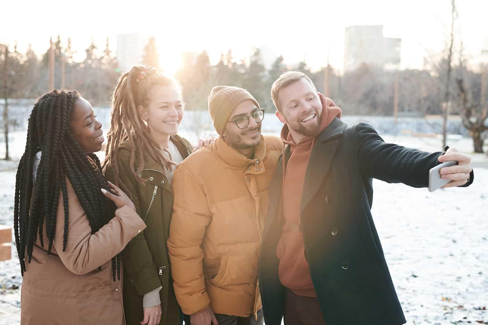 Gruppe glücklicher Freunde, die ein Selfie nehmen, das auf dem Schnee steht
