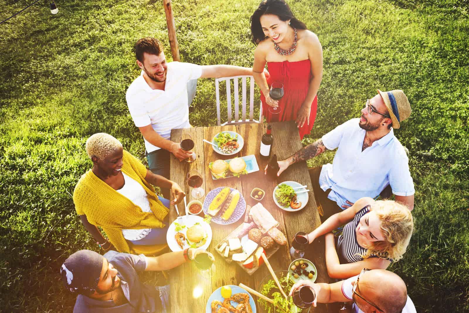Im Garten isst eine Gruppe von Freunden zu Mittag und hat Spaß