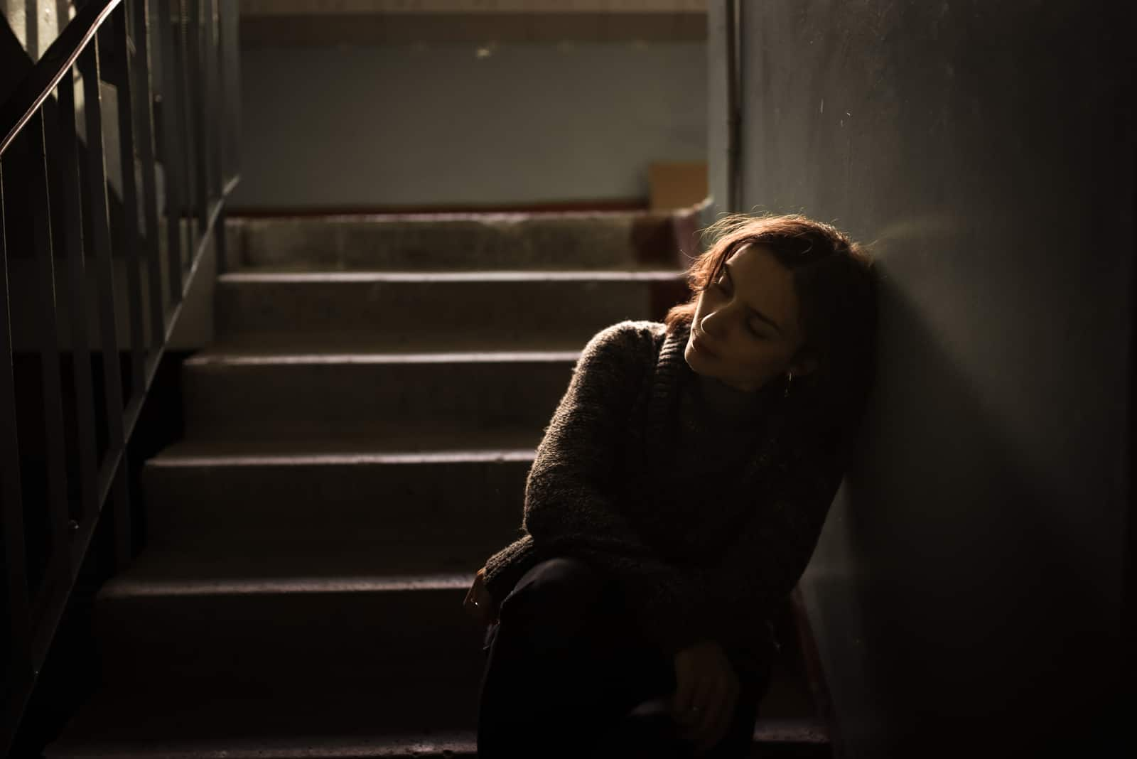 Im Haus auf der Treppe sitzt eine depressive Frau