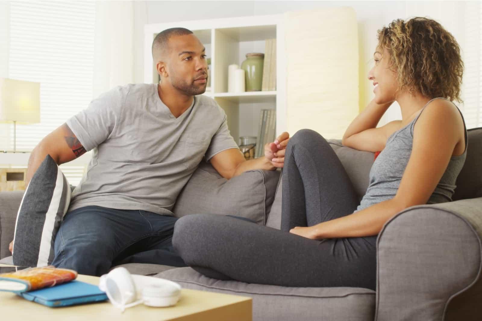 Im Wohnzimmer auf dem Sofa spricht ein liebevolles Paar