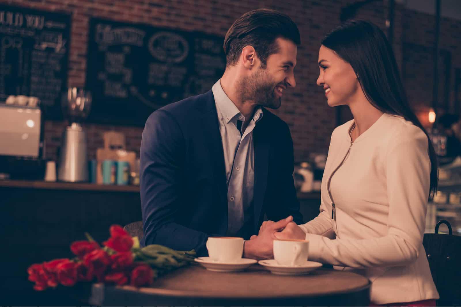 In einem Café trinkt ein glückliches romantisches Paar verliebt Kaffee