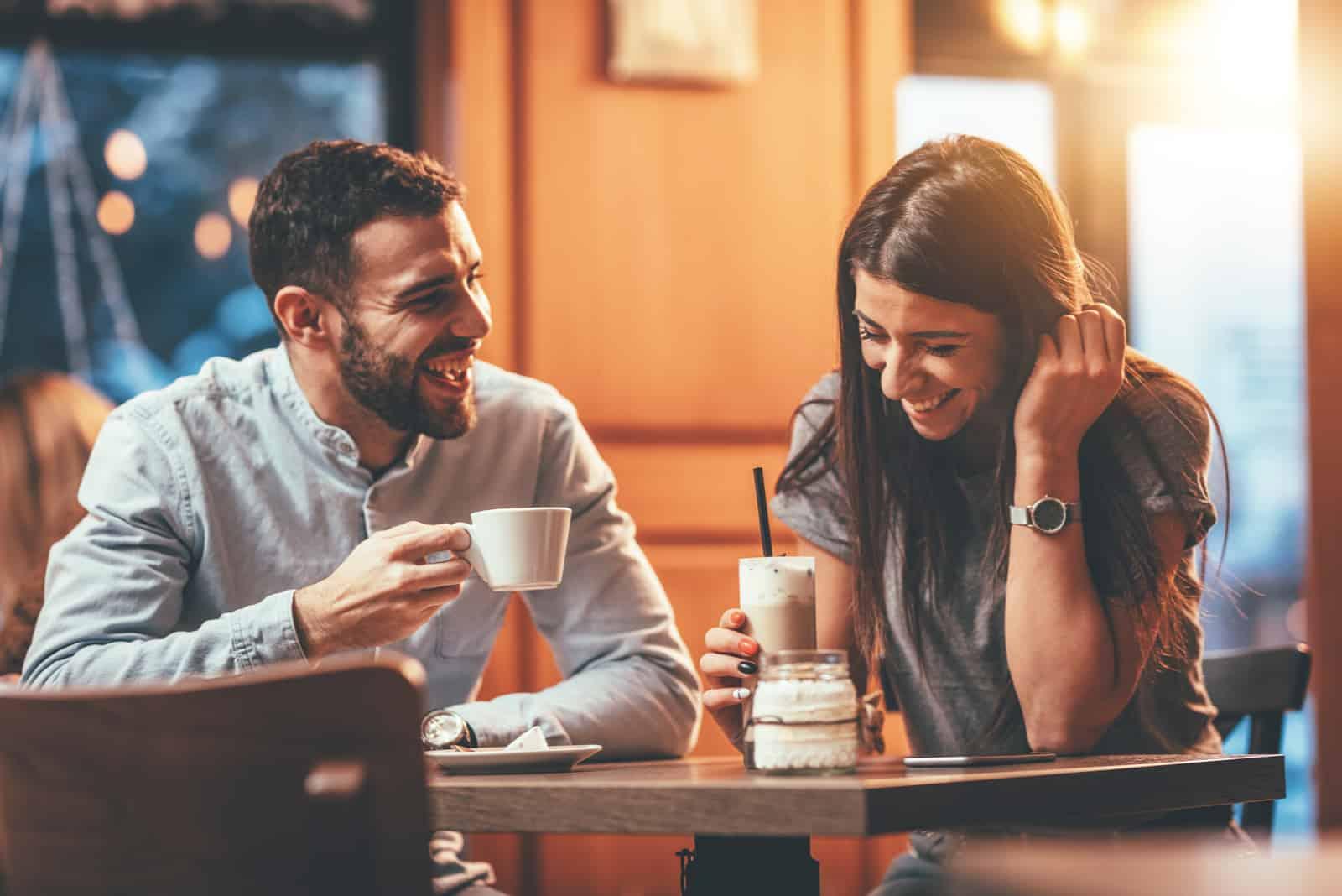 In einem Café trinkt ein lächelndes Paar Kaffee und redet