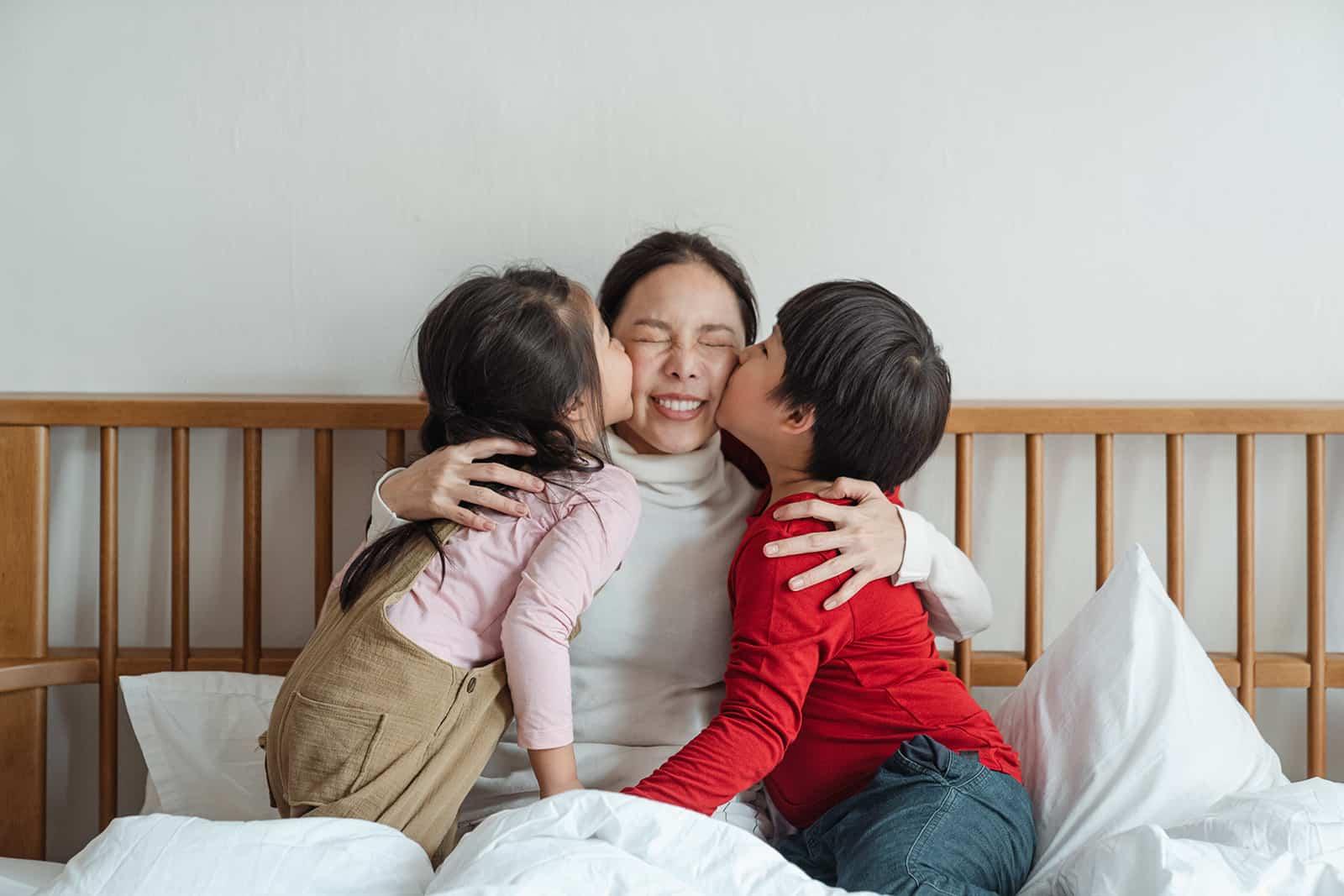 Kinder küssen ihre Mutter auf eine Wange, während sie auf dem Bett sitzen