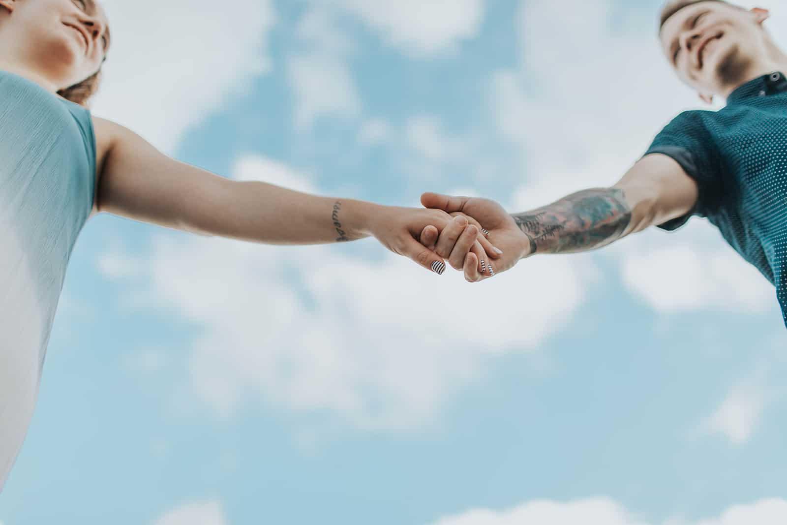 liebendes Paar, das Hände hält, die unter dem blauen Himmel stehen