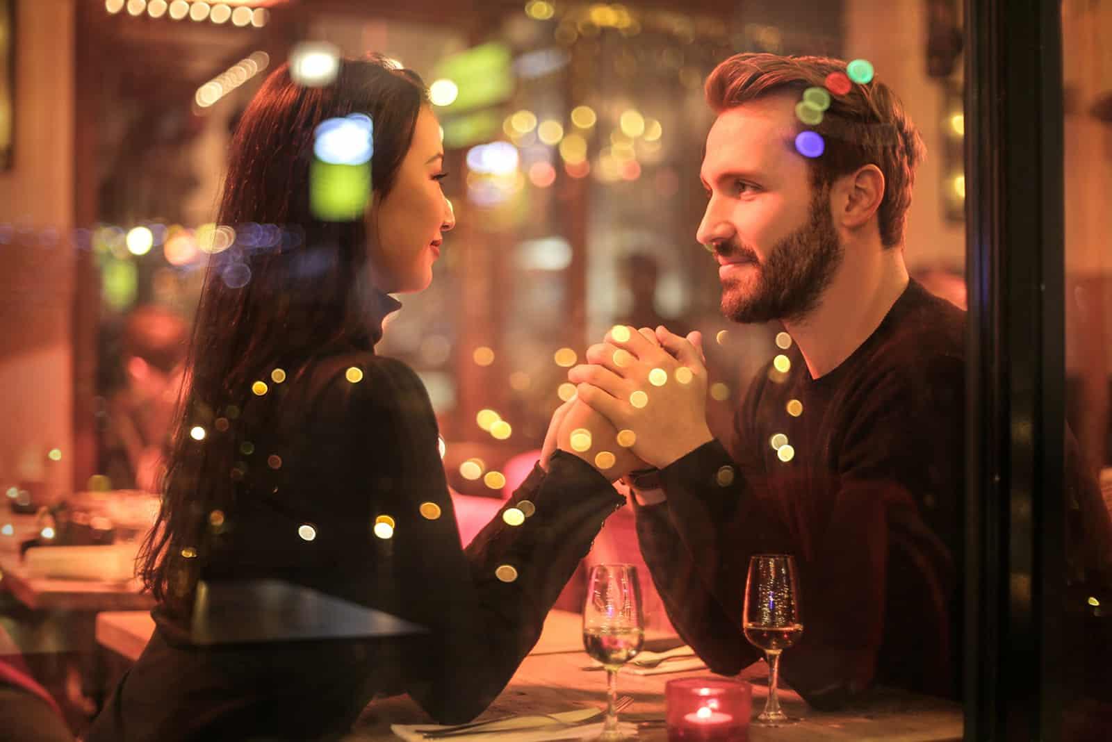 Liebespaar Händchen haltend in einem romantischen Restaurant
