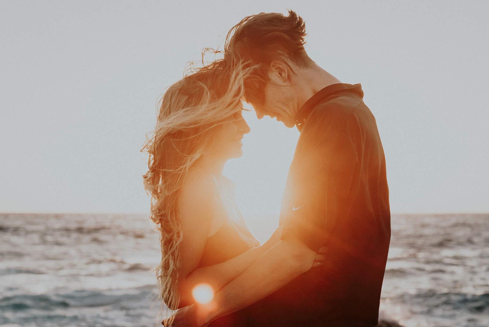 Liebespaar, das sich während des Sonnenuntergangs in der Nähe des Meeres umarmt