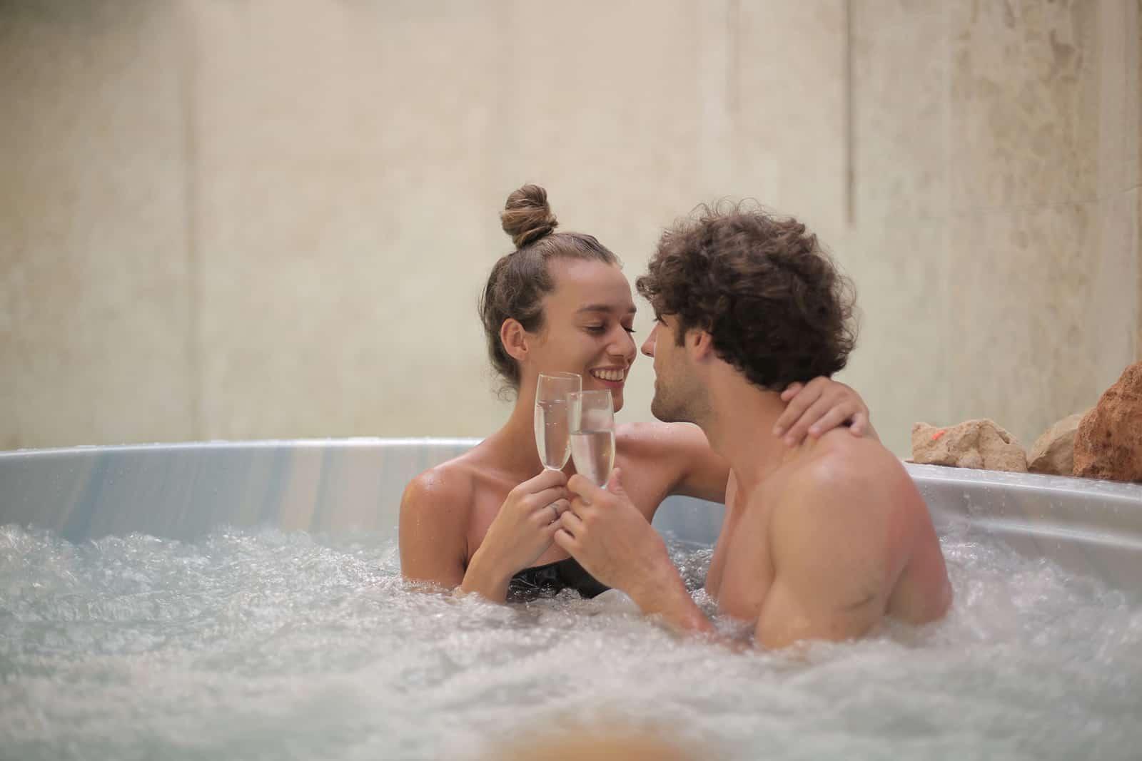 Liebespaar trinkt Champagner im Whirlpool