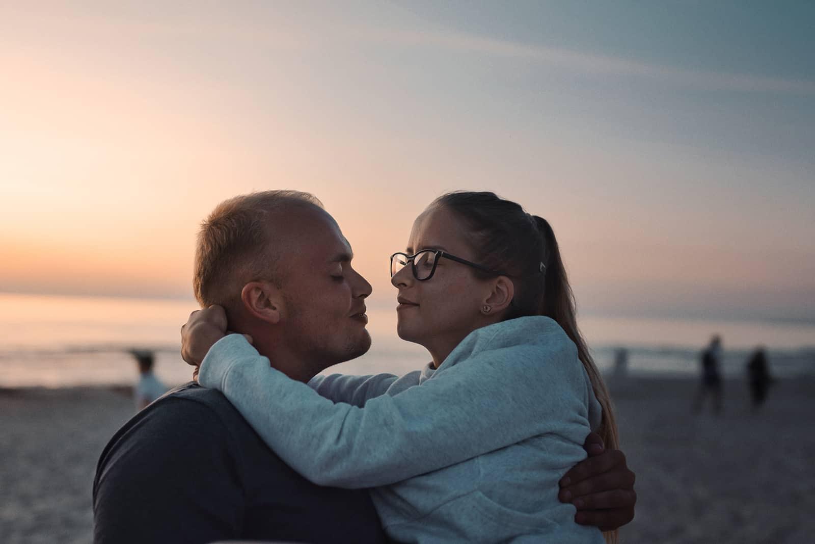 Ein liebevolles Paar, das sich am Strand umarmt