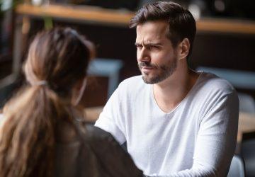 ein verwirrter Mann, der mit einer Frau auf einem Date sitzt